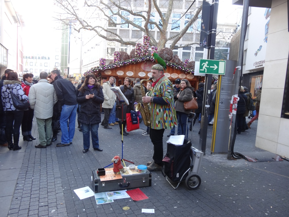 Street performer (and his parrot) playing Christmas music on his Saxophone.