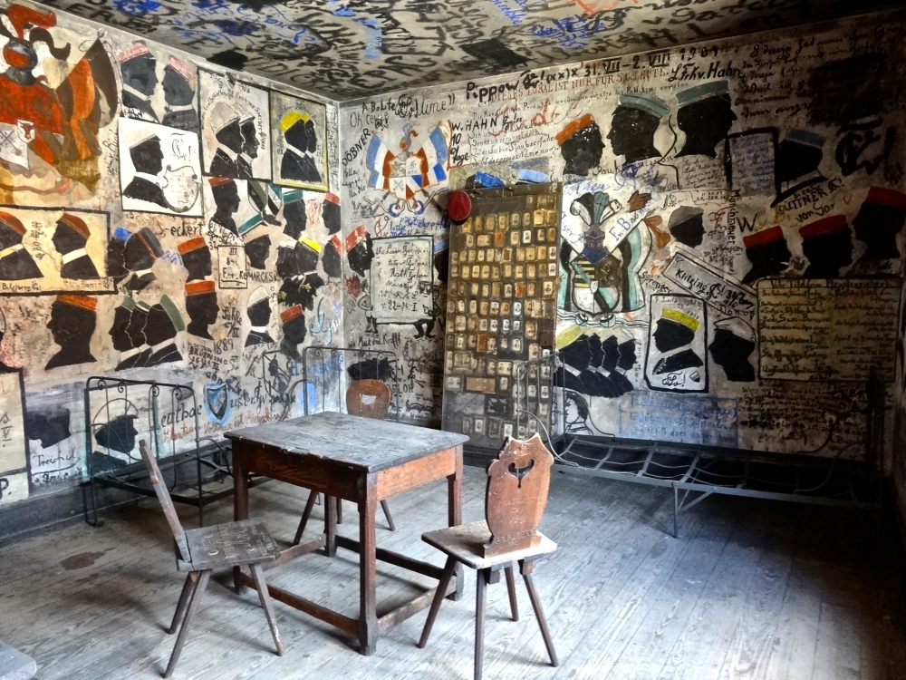 Inside the student prison's cells, everything is covered by the prisoners' names, portraits and verses