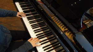 Leona playing a Steinway grand piano.