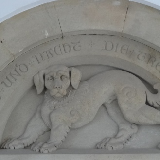 "At the entrance, a dog stone figure can be found, as a symbol of fidelity. The words say ""Faithfulness keeps watch by day and night"""
